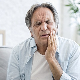 Older man sitting down and rubbing jaw due to toothache