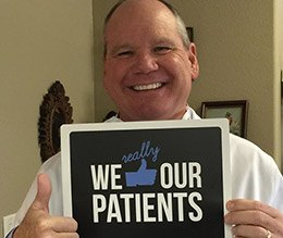 Dr. Hutto holding a we like our patients sign