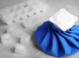 a blue ice pack with ice cubes next to it