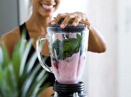 a person smiling and blending a smoothie together