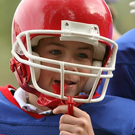 Young boy placing red mouthguard
