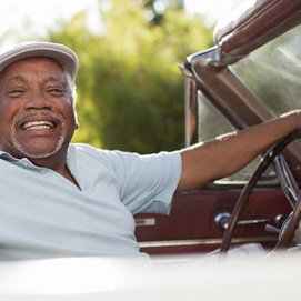 smiling person in a golfing cap driving an old convertible