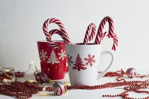 Two coffee cups holding candy canes and surrounded by holiday lights, ribbons and ornaments