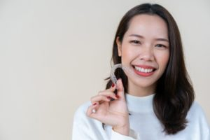Woman smiling while holding Invisalign